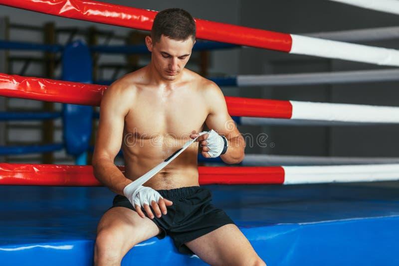 El hombre del boxeador está envolviendo las manos con los abrigos del boxeo foto de archivo libre de regalías