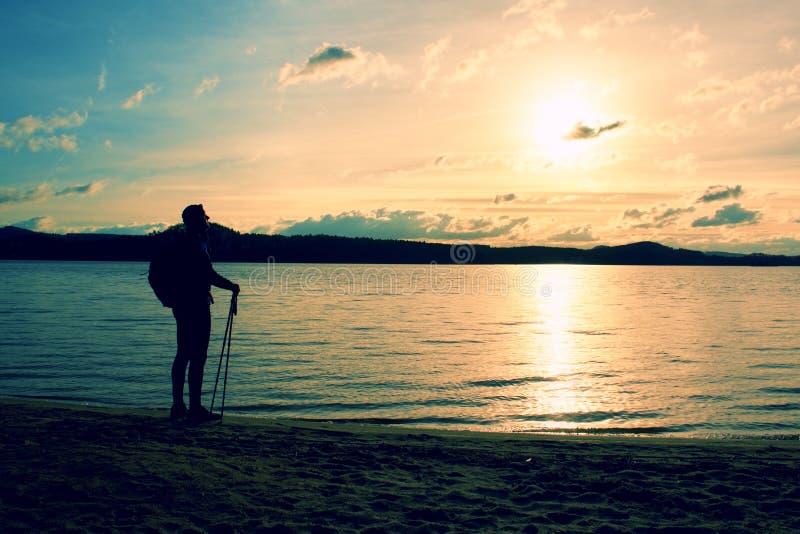 El hombre del caminante en ropa de deportes oscura y con la mochila deportiva que se coloca en la playa, relajándose y disfruta d imagen de archivo libre de regalías