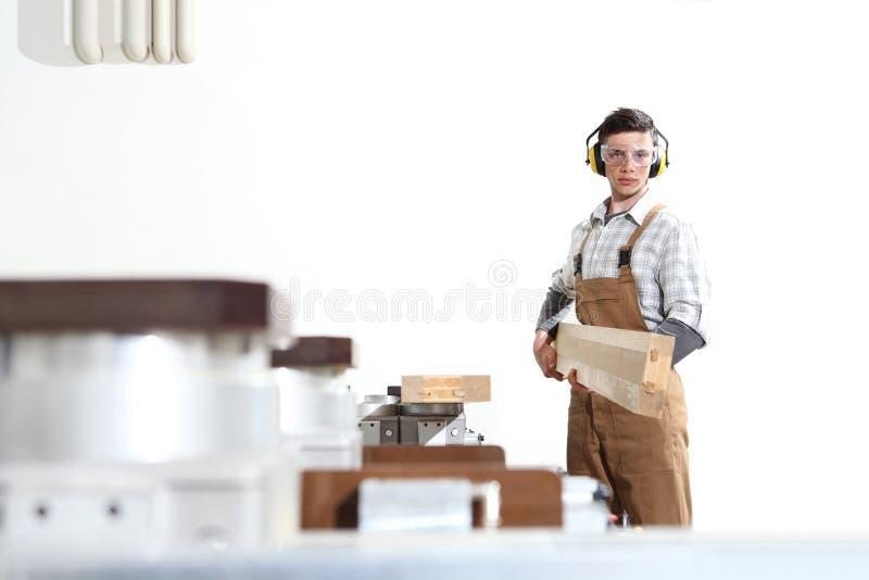 El hombre del carpintero trabaja con los tablones de madera en la carpinter?a, con el centro de control num?rico de ordenador, m? fotos de archivo libres de regalías