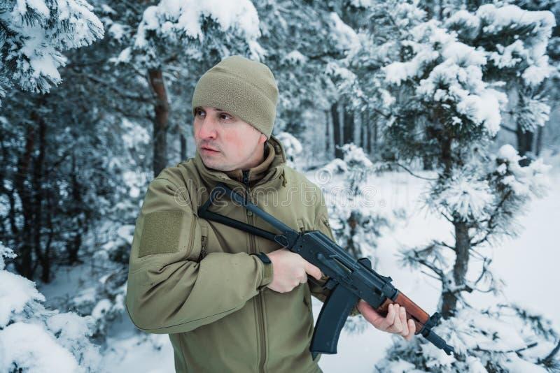 El hombre del cazador se vistió en la ropa del camuflaje que se colocaba en el invierno imagen de archivo