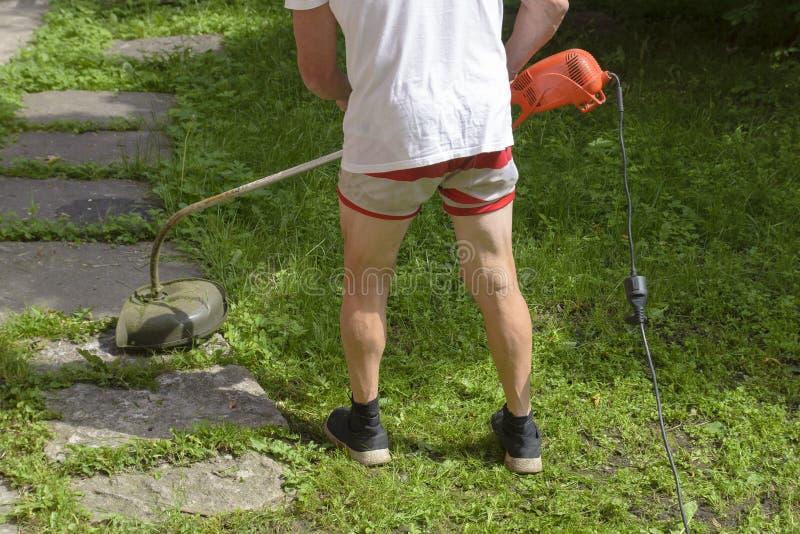 El hombre del cortacésped en pantalones cortos en el calor, siega el condensador de ajuste de la hierba fotos de archivo