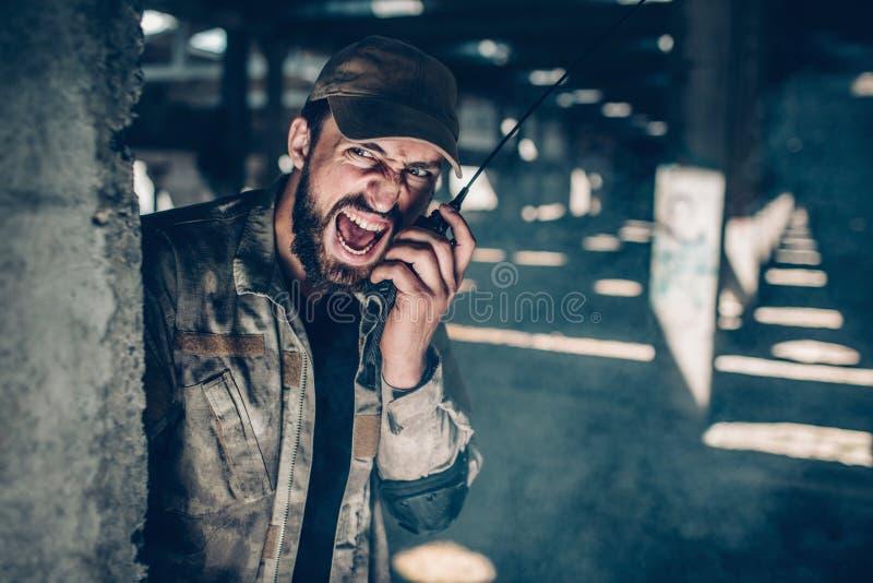El hombre del ejército está sosteniendo la radio portátil cerca de su cara y está hablando muy ruidosamente Él está gritando El i foto de archivo