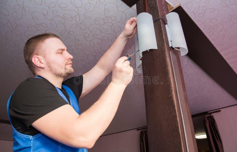 El hombre del electricista que trabaja en luz exterior, instala la lámpara de reemplazo del LED en casa Concepto de mantenimiento imagenes de archivo