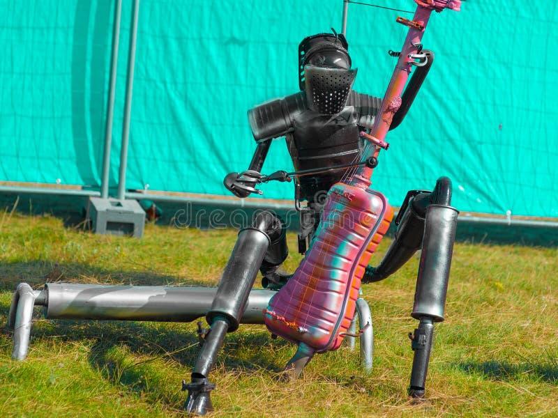 El hombre del hierro juega el bajo doble, el robot toca el violoncelo fotos de archivo