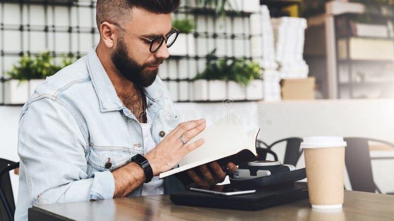 El hombre del inconformista en vidrios se está sentando en el café, leyendo notas en cuaderno En la tabla es el ordenador portáti imágenes de archivo libres de regalías