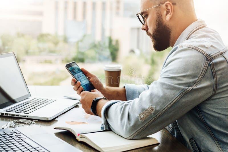 El hombre del inconformista se sienta en café, utiliza smartphone, trabaja en dos ordenadores portátiles El hombre de negocios le fotos de archivo