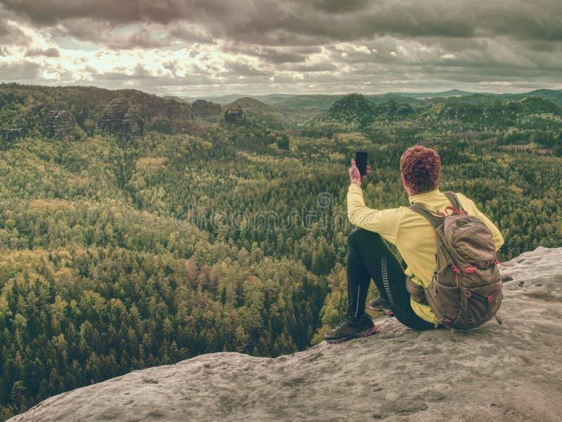 El hombre del jengibre toma las fotos con el teléfono elegante en pico rocoso fotografía de archivo