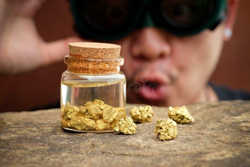El hombre del ladrón sea pasmado mirando el oro en la botella foto de archivo
