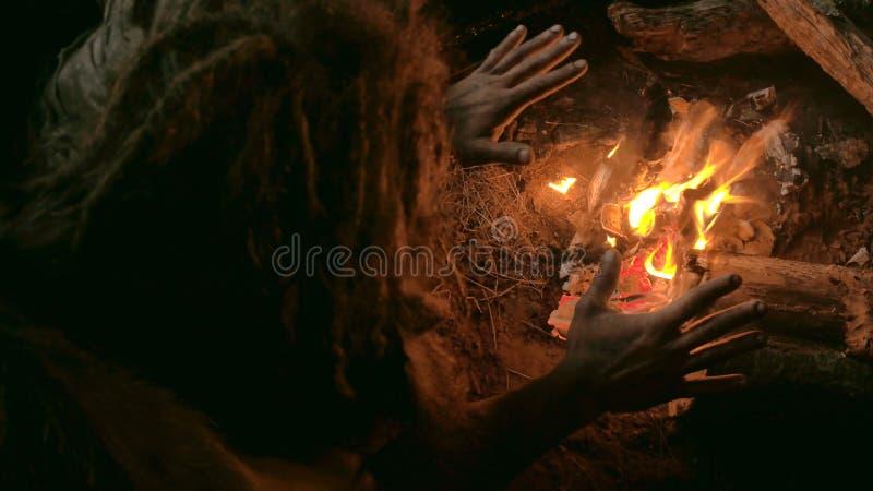 El hombre del Neanderthal se calienta las manos por la primera hoguera en su cueva metrajes