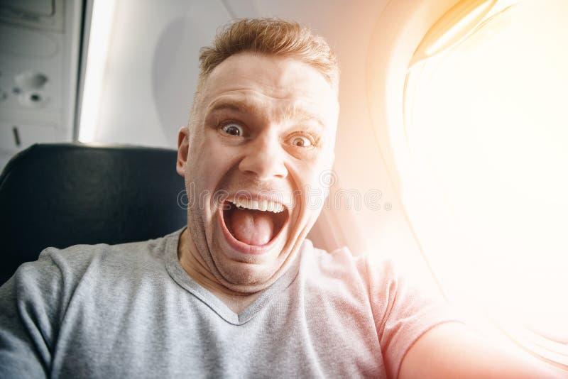 El hombre del pasajero en el avión agarra a su cabeza, asustada de alturas y de vuelo Expresión del grito y del grito fotos de archivo libres de regalías
