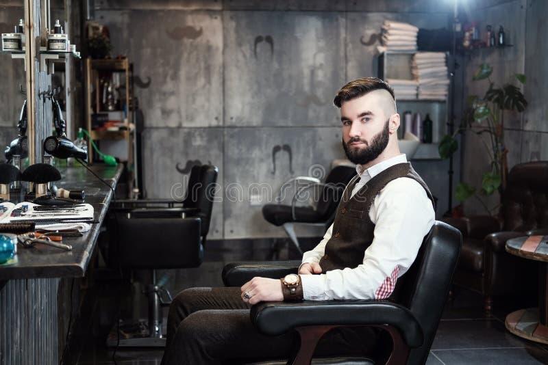 El hombre del peluquero afeita a un cliente con una barba en una barbería imagen de archivo