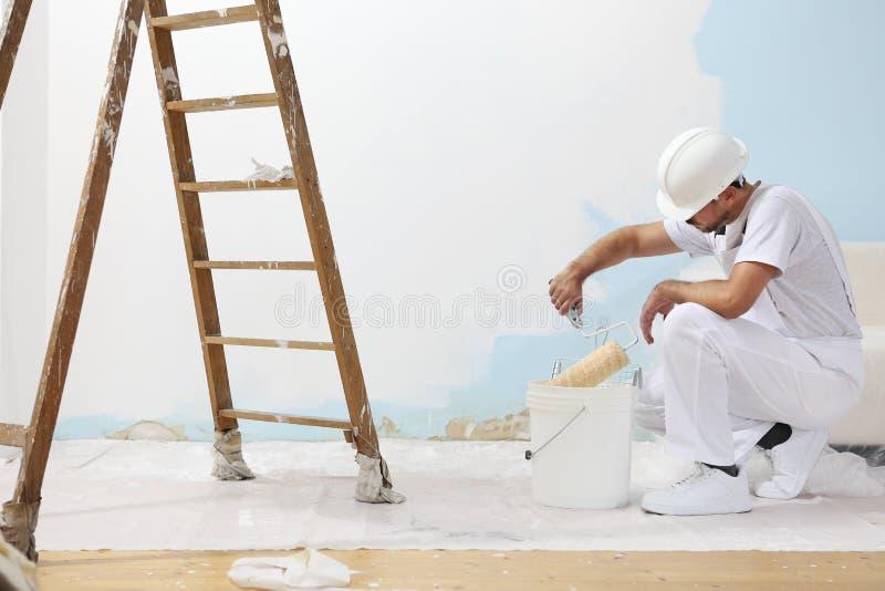 El hombre del pintor en el trabajo toma el color con el rodillo de pintura del b foto de archivo libre de regalías