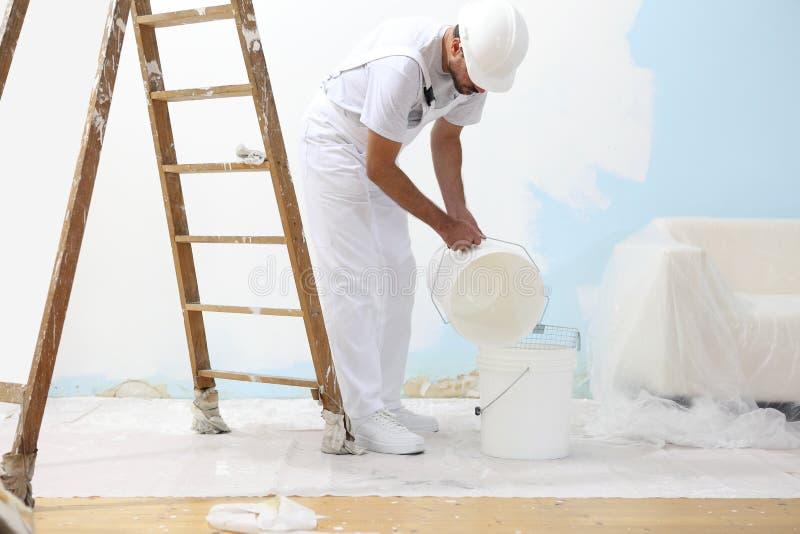 El hombre del pintor en el trabajo vierte en el color del cubo para pintar foto de archivo libre de regalías