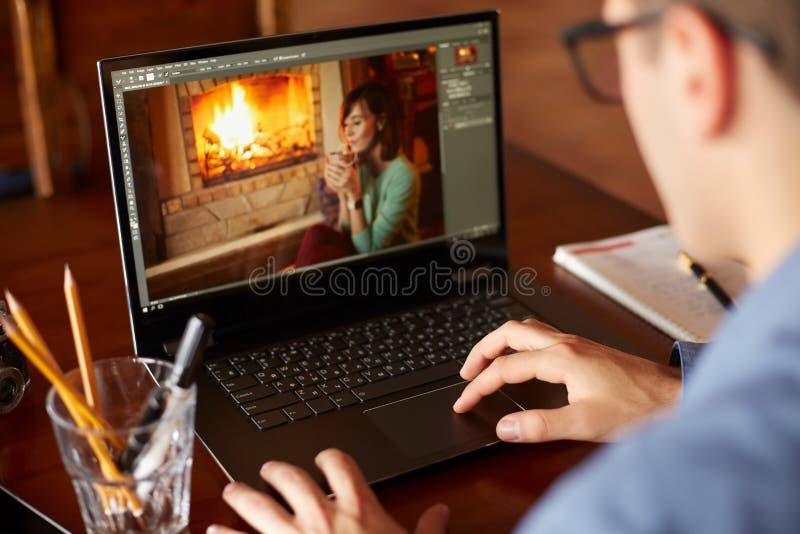 El hombre del retoucher del Freelancer trabaja en el ordenador portátil con la foto que corrige software Fotógrafo o diseñador en imagenes de archivo