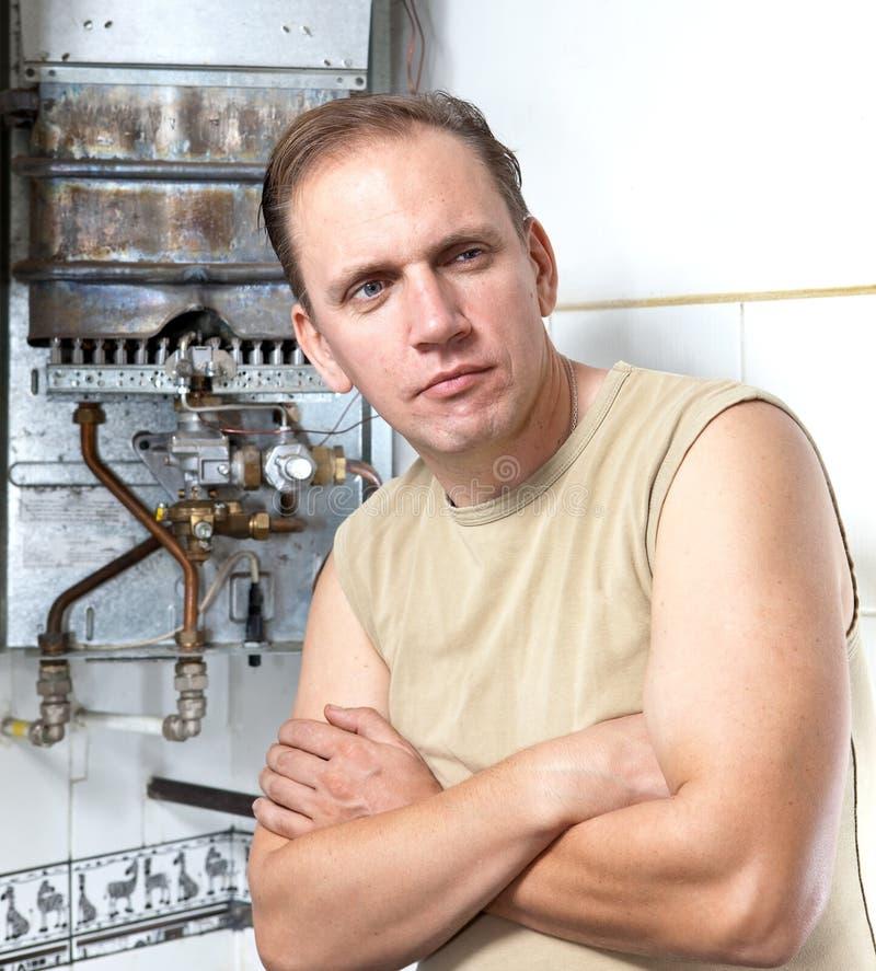El hombre del retrato está trastornado, el calentador de agua del gas se ha roto imagen de archivo