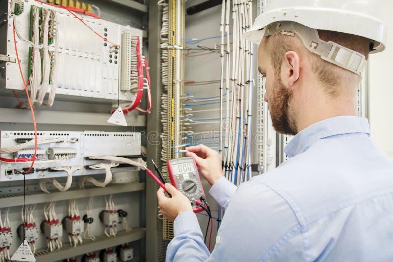 El hombre del servicio con el multímetro en manos ajusta el panel de control eléctrico El ingeniero en casco prueba el dispositiv fotos de archivo libres de regalías