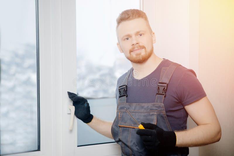 El hombre del trabajador instala ventanas y puertas plásticas con blanco de aislamiento doble imágenes de archivo libres de regalías