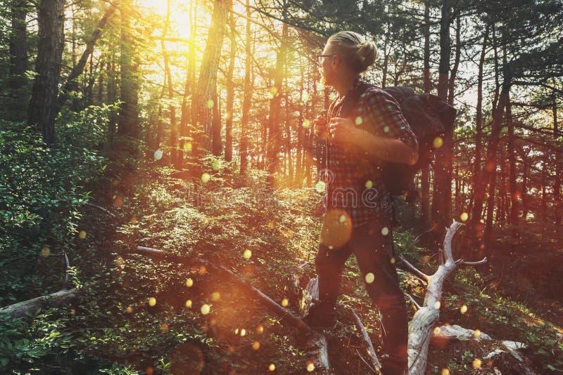 El hombre del viajero con la mochila camina a través del bosque y disfruta de la vista del sol Concepto de aventura, de caminar y fotografía de archivo
