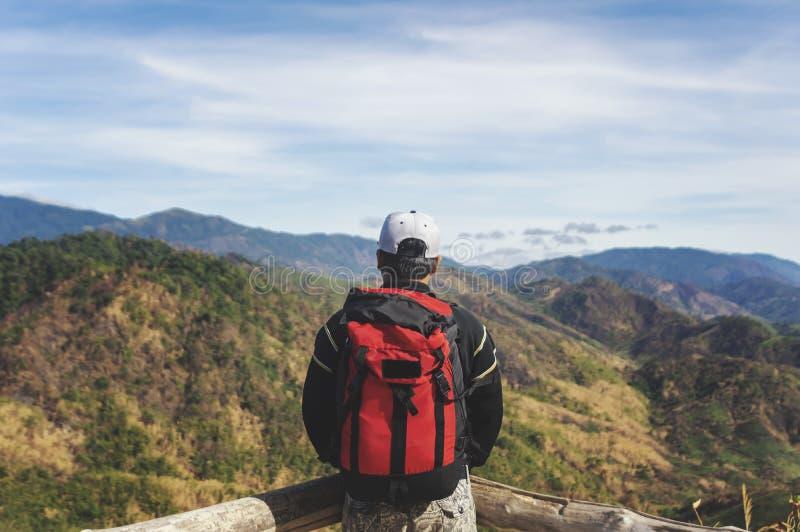 El hombre del viajero con las montañas de la mochila ajardina en fondo imagen de archivo libre de regalías