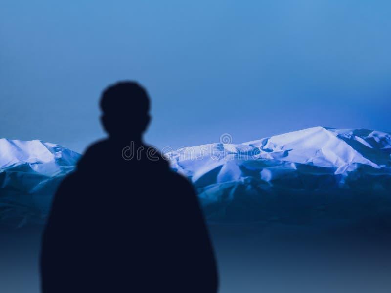 El hombre del viajero de la silueta mira la cordillera montañés del deportista antes de subir Forma de vida del active del concep imagen de archivo libre de regalías