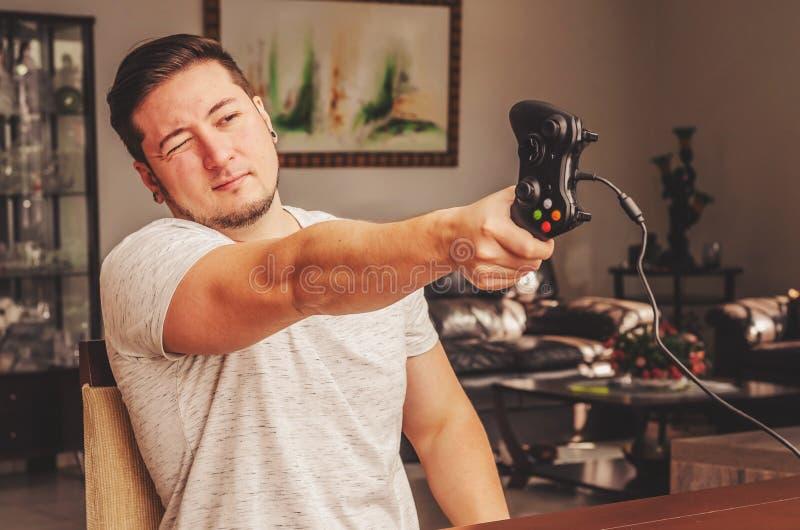 El hombre del videojugador que celebra un control del videojuego le gusta un arma fotografía de archivo libre de regalías