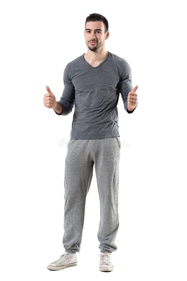 El hombre deportivo joven feliz del ajuste que muestra los pulgares sube el gesto que sonríe en la cámara foto de archivo libre de regalías