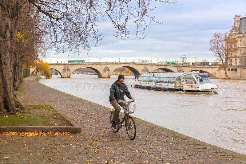 El hombre deportivo joven monta una bicicleta en el Sena fotografía de archivo libre de regalías