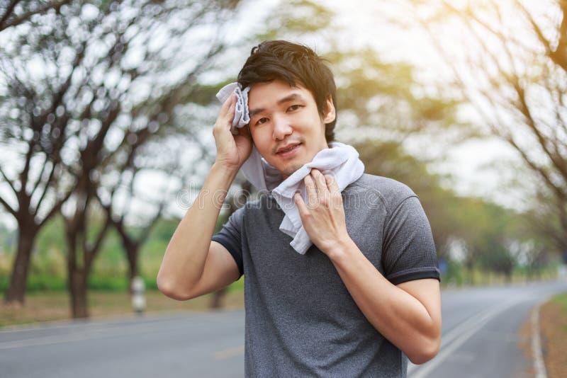 El hombre deportivo joven que descansaba y que limpiaba el suyo sudó con una toalla después imagen de archivo