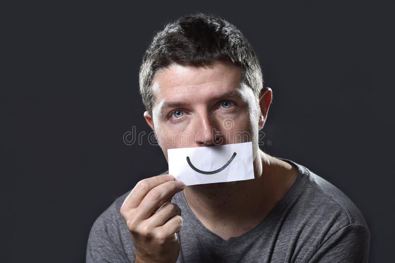 El hombre deprimido joven perdió en la tristeza y el dolor que se sostenía de papel con smiley en su boca en concepto de la depre fotografía de archivo libre de regalías