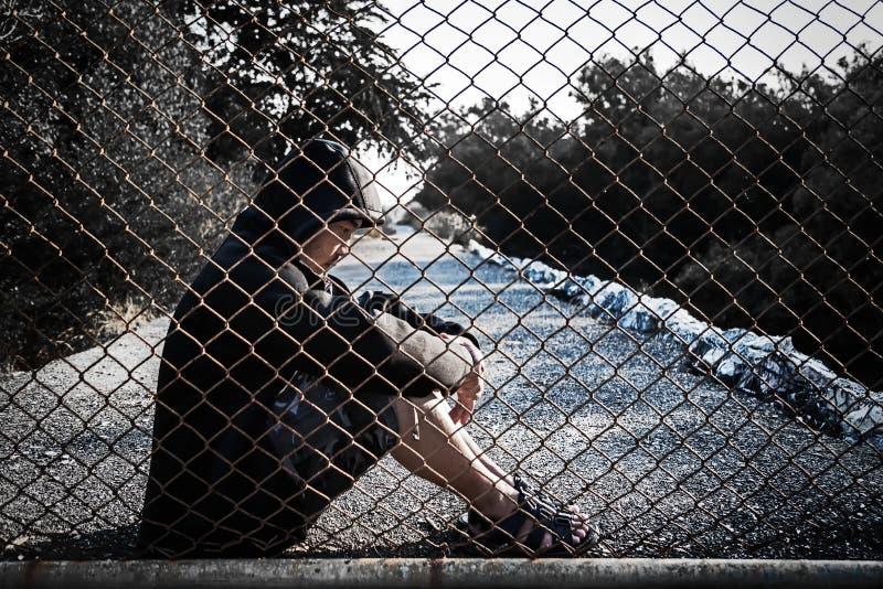 El hombre deprimido que lleva una sudadera con capucha negra que se sienta en la tierra es s imágenes de archivo libres de regalías