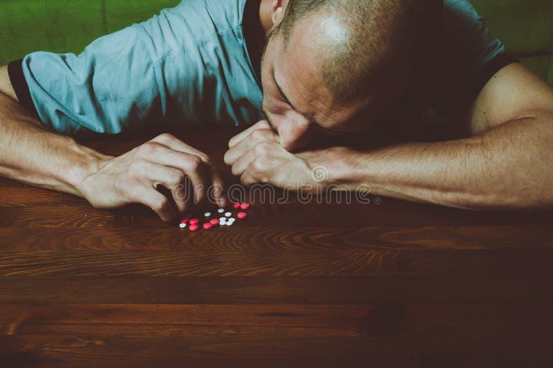 El hombre deprimido que sufre de la depresión suicida quiere confiar suicidio tomando las drogas fuertes del medicamento y las pí imágenes de archivo libres de regalías