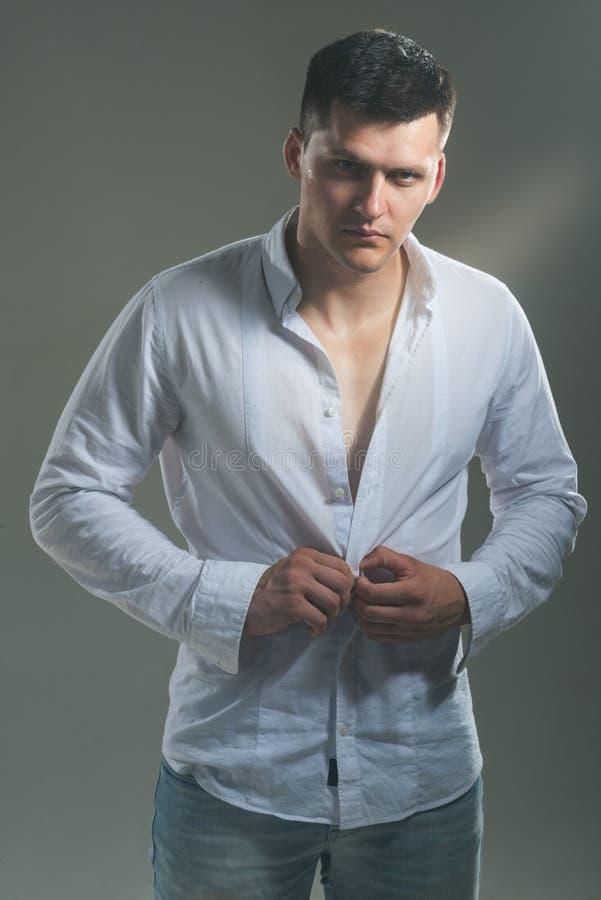 El hombre desabrocha la camisa de moda El machista joven desnuda la camisa blanca individuo con la cara seria Modelo atractivo co fotos de archivo