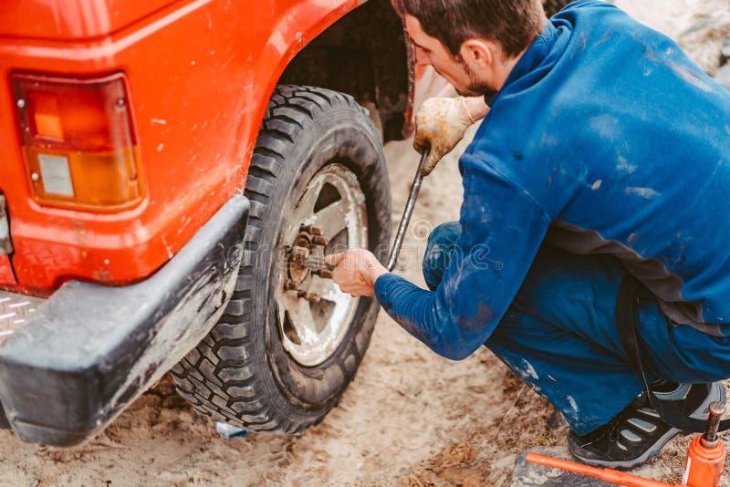 El hombre desatornilla los pernos en la rueda foto de archivo