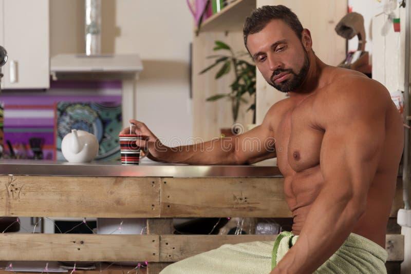 El hombre descamisado del soltero del músculo desayuna en cocina foto de archivo libre de regalías