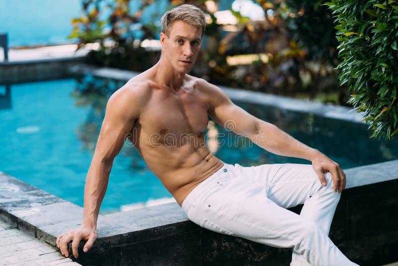 El hombre descamisado hermoso fuerte en los pantalones blancos se sienta en piscina en jard?n Modelo de la aptitud que presenta e imagenes de archivo