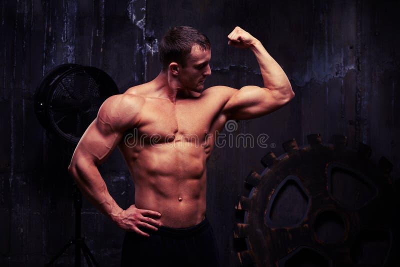 El hombre descamisado que dobla los músculos que muestran el gran alivio el suyo arma a fotos de archivo