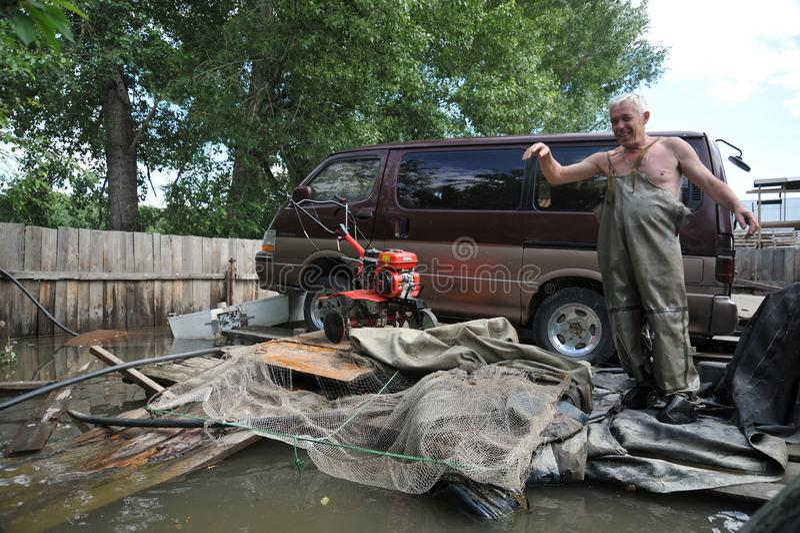 El hombre desconocido ahorra un coche durante una inundación en las altiplanicies creadas foto de archivo libre de regalías