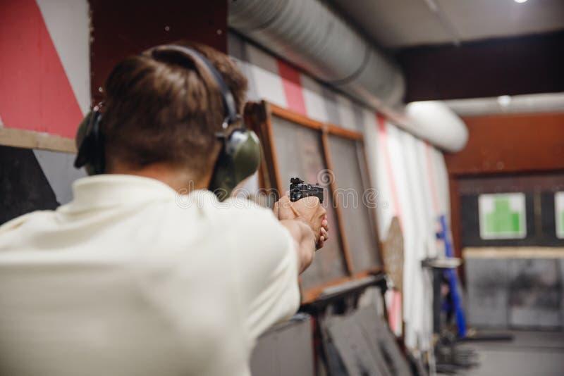 El hombre dirige la pistola del arma del arma de fuego en la gama o la radio de tiro de leña de la blanco imagen de archivo