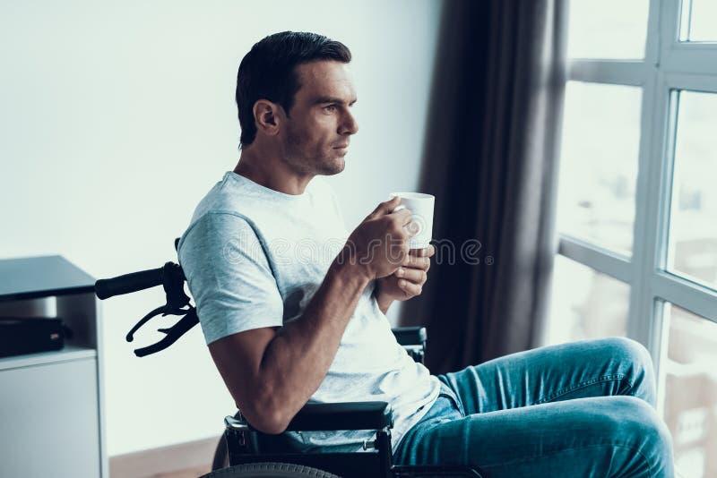 El hombre discapacitado hermoso se sienta en silla de ruedas con la taza fotos de archivo libres de regalías