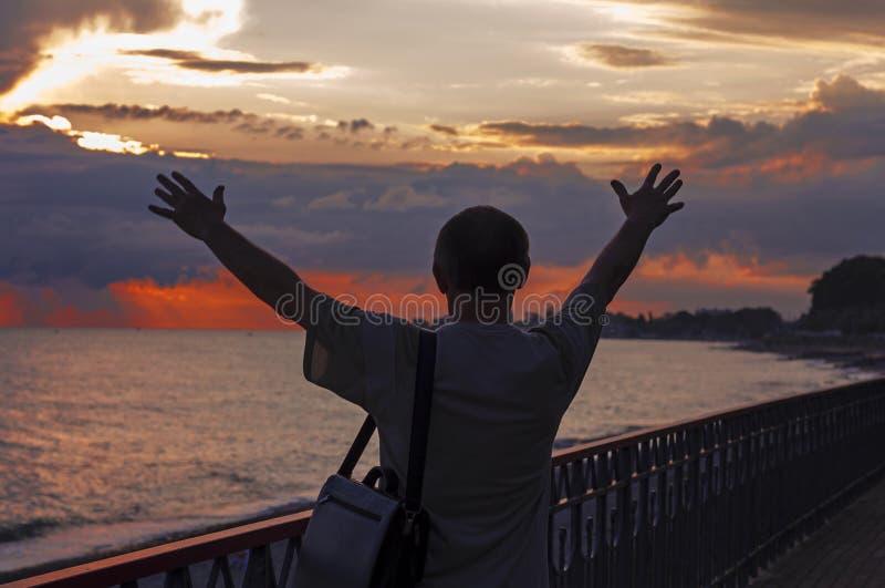 El hombre disfruta de puesta del sol en el mar fotografía de archivo libre de regalías
