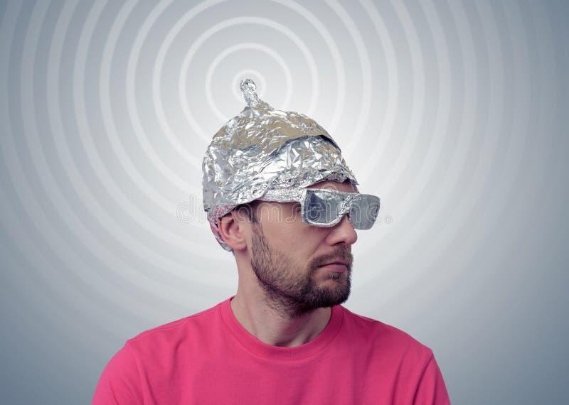 El hombre divertido barbudo en un casquillo del papel de aluminio envía señales foto de archivo