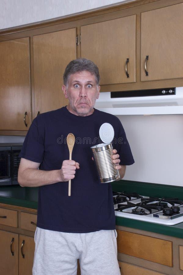 El hombre divertido del soltero que cocina la cena come de la poder de estaño imagen de archivo