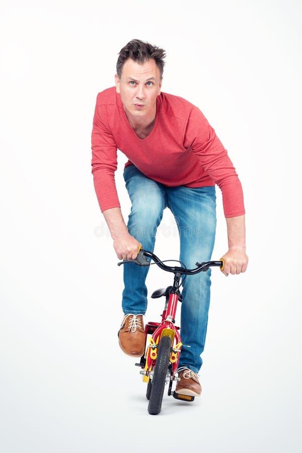 El hombre divertido en vaqueros y una camiseta roja está rodando en una bici de los niños Front View foto de archivo libre de regalías