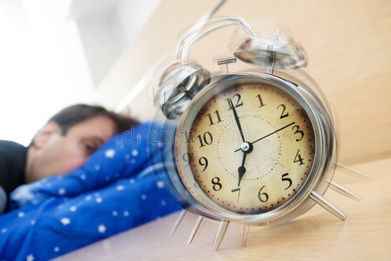 El hombre durmiente mira el despertador en la tabla foto de archivo libre de regalías