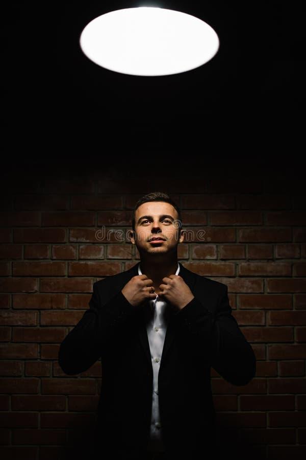 El hombre elegante de la moda de los jóvenes en smoking está llevando a cabo ambas manos en el suyo fotos de archivo libres de regalías