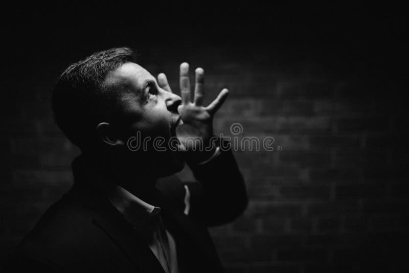 El hombre elegante de la moda de los jóvenes en smoking está llevando a cabo ambas manos en el suyo foto de archivo libre de regalías