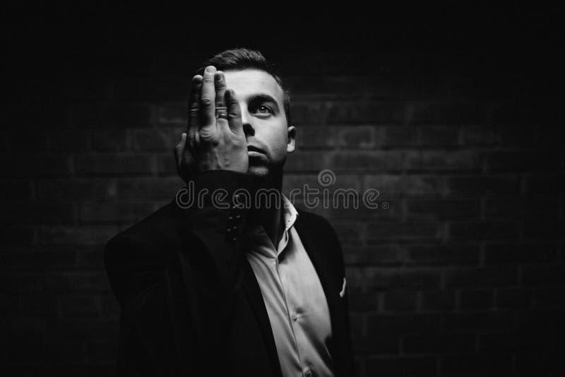 El hombre elegante de la moda de los jóvenes en smoking está llevando a cabo ambas manos en el suyo imagen de archivo libre de regalías
