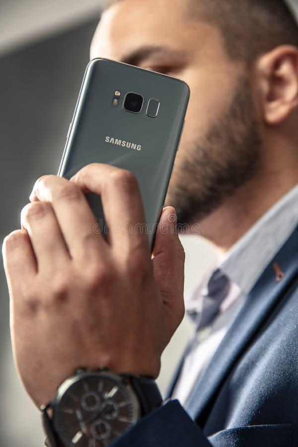 El hombre elegante en traje sostiene su smartphone fotografía de archivo libre de regalías
