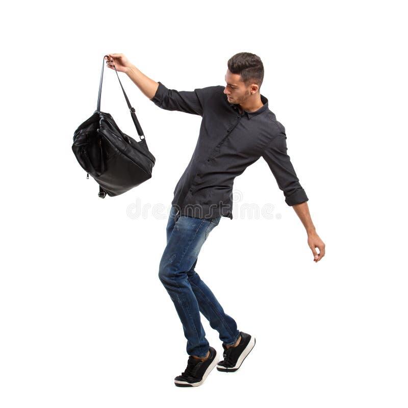 El hombre elegante joven vestido en una camisa negra y vaqueros presenta con la mochila negra en el fondo blanco fotos de archivo