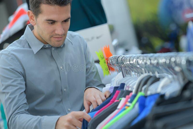 El hombre elige la camiseta en tienda fotos de archivo